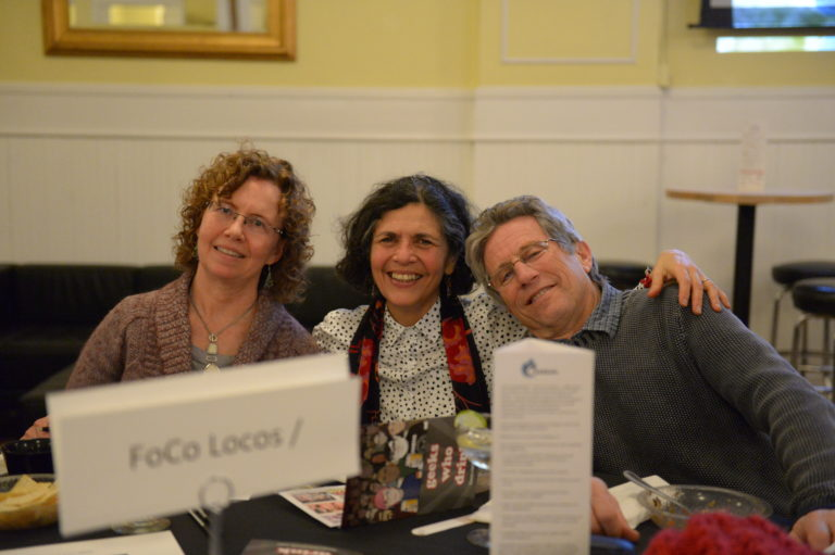 Image of three people sitting at table smiling
