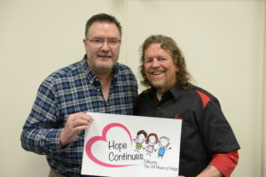 Image of Brian and Todd holding sign saying hope continues