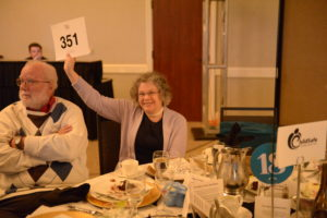Image of woman holding up a number